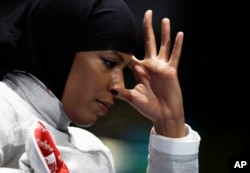Ibtihaj Muhammad of the United States reacts after losing against Cecilia Berder of France in the women's individual saber fencing event at the 2016 Summer Olympics in Rio de Janeiro, Brazil, Aug. 8, 2016.