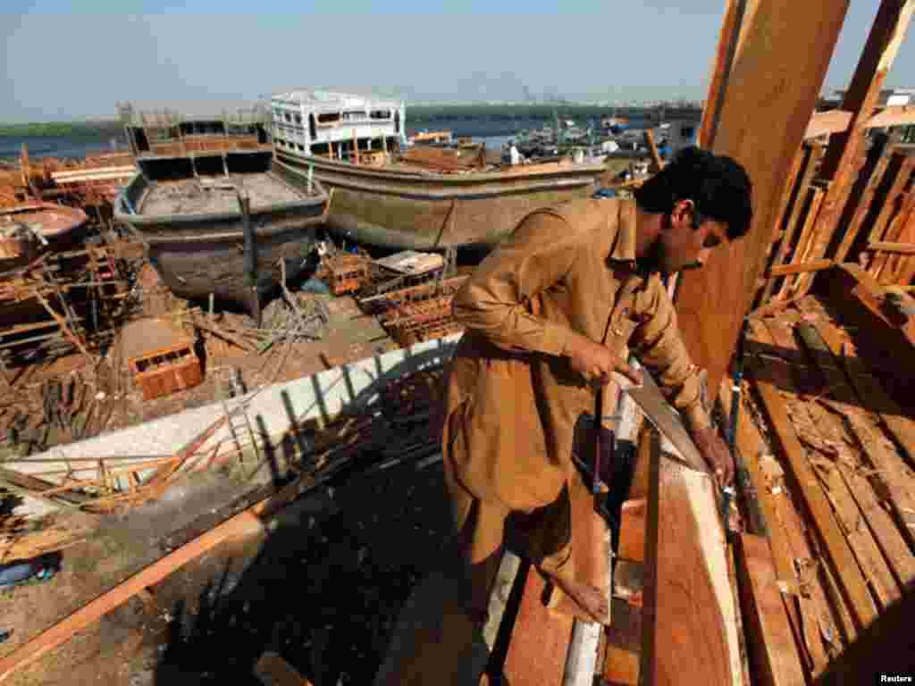 کراچی کی بندرگاہ پر ایک کشی ساز کشتی کی تیاری میں مصروف ہے