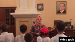 """""""One should wait for a while to make comments on history,"""" says Luiza Khatueva, a tour guide at the Akhmad Kadyrov Museum, seen here before a group of school children, with a portrait of President Vladimir Putin in the background."""