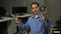 NASA astrophysicist Zaven Arzouman holds a model of the NICER telescope lenses.