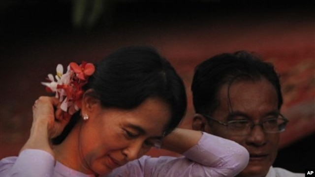 Myanmar's pro democracy leader Aung San Suu Kyi, places flowers from a supporter in her hair after her release from house arrest in Rangoon, Burma, 13 Nov 2010