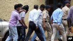 Polisi India mengawal salah seorang tersangka (ditutup kepalanya) kasus perkosaan di Mumbai (24/8).