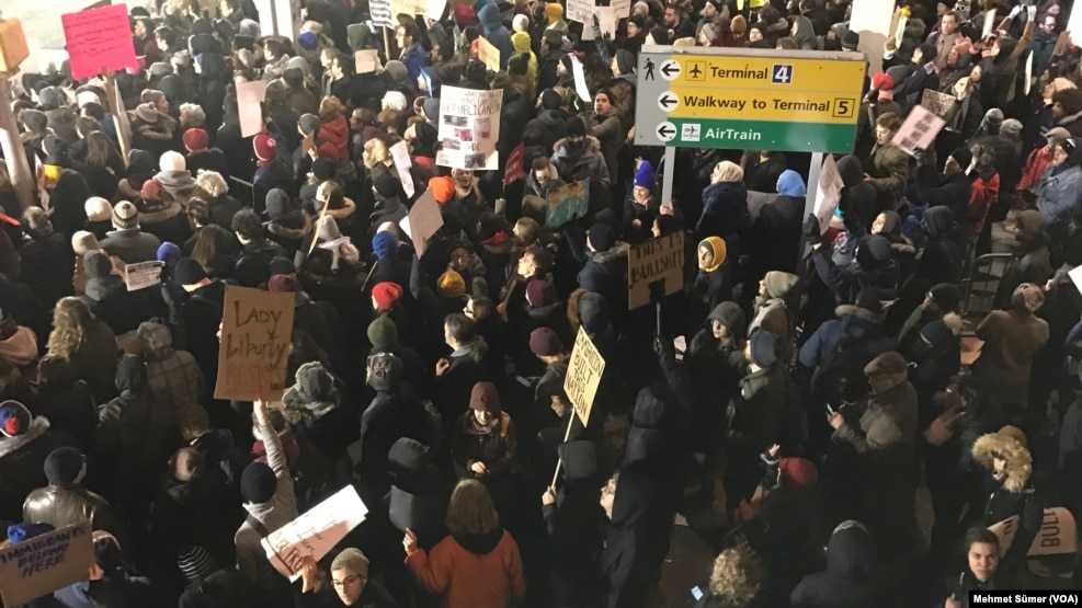 Des centaines de manifestants sont réunis à l'aéroport JFK, à New York, le 28 janvier 2017. (VOA/Mehmet Sümer)