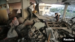 A Palestinian woman, left, cries inside her damaged house, which police said was targeted in an Israeli airstrike in Gaza City, July 17, 2014.