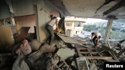 巴勒斯坦妇女在被毁坏的房子里哭泣,警察说是以色列的攻击毁坏了房子