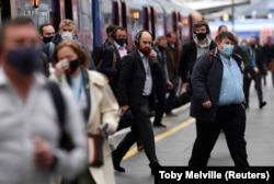 Para pelaju di stasiun kereta Waterloo saat jam sibuk pagi hari di tengah pelonggaran pembatasan pandemi COVID-19, di London, Inggris, Rabu, 19 Mei 2021. (Foto: Toby Melville/Reuters)