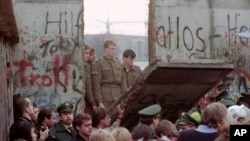 East German border guards look through a hole in the Berlin wall after demonstrators pulled down one segment of the wall at Brandenburg gate Saturday, November 11, 1989. (AP Photo/Lionel Cironneau)