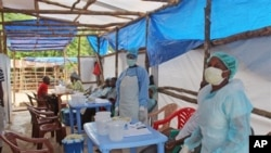 In this photo taken on Sunday, July 27, 2014, Medical personnel inside a clinic taking care of Ebola patients in the Kenema District on the outskirts of Kenema, Sierra Leone. Liberia President Ellen Johnson Sirleaf has closed some border crossings and o
