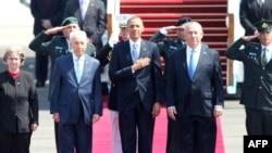 2013年3月20日星期三奥巴马总统(中)抵达本•古里安机场,受到以色列总统佩雷斯(左)和总理内塔尼亚胡(右)的欢迎。