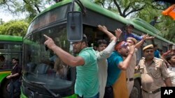 Activists of the youth wing of India's ruling party Bharatiya Janata Party shout slogans as they are detained during a protest against the slaughter of a calf by Congress party's youth wing members, in New Delhi, May 30, 2017.