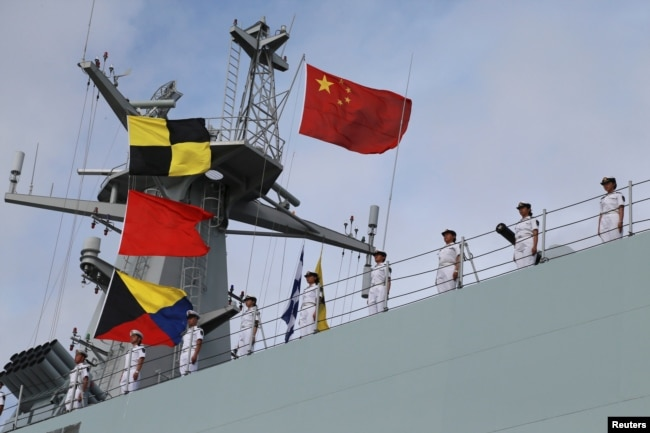 Soldiers of China's People's Liberation Army (PLA) stand on a ship sailing off from a military port in Zhanjiang, Guangdong province, July 11, 2017.