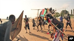 Former militia leader Gabriel Tanginye, left, participates in a traditional dance with dancers from the Nuer tribe at the Juba airport upon his arrival in the southern capital to hold peace talks with the president and army leadership, 14 Oct 2010 (file p