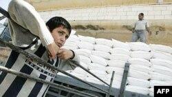 Một cậu bé Palestine đứng bên cạnh chiếc xe tải chở hàng viện trợ của USAID