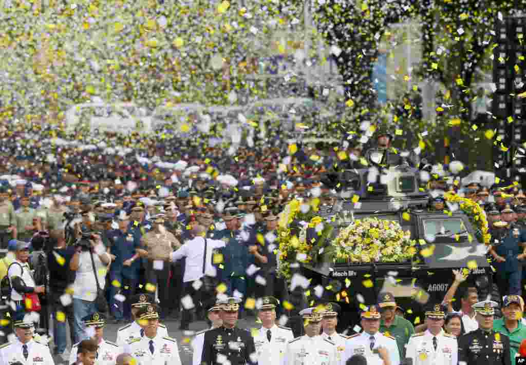 "Yellow confetti rain on the military component during the 30th anniversary celebration at suburban Quezon city, northeast of Manila, the Philippines, of the ""People Power Revolution"" that toppled the 20-year-rule of the late strongman Ferdinand Marcos."