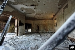 FILE - A Libyan man walks in the damaged U.S. consulate after an attack the night of Sept. 11, 2012, in Benghazi, Libya.
