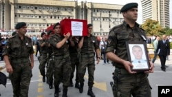 FILE - Turkish police officers carry the coffin of Turkish police special operations officer Sahin Polat Aydin, one of the four officers killed in a landmine attack attributed to PKK militants in Silopi, southeastern Turkey, during a ceremony in Ankara, Aug. 11, 2015.