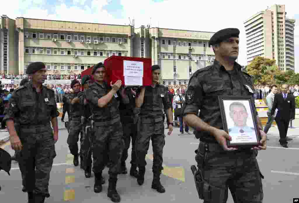 Turkish police officers carry the coffin of Turkish police special operations officer Sahin Polat Aydin, one of the four officers killed Monday in a landmine attack attributed to militants of the Kurdistan Workers' Party, or PKK, in Silopi, southeastern Turkey, during a ceremony in Ankara, Aug. 11, 2015.