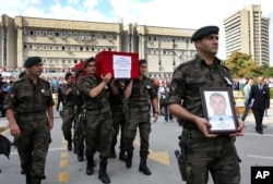 FILE - Turkish police officers carry the coffin of Turkish police special operations officer Sahin Polat Aydin, one of the four officers killed in a landmine attack attributed to PKK militants.