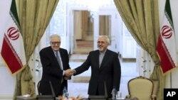 Menteri Luar Negeri Iran Mohammad Javad Zarif (kanan) berjabat tangan dengan utusan PBB-Liga Arab untuk Suriah Lakhdar Brahimi pada konferensi pers di Tehran (26/10).