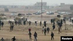 25일 이라크 군용차에 돌멩이를 던지며 저항하는 시위대.