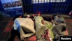 FILE - People sleep on makeshift beds on a street, where Venezuelan migrants gather to spend the night, in Maicao, Colombia, Feb. 15, 2018.