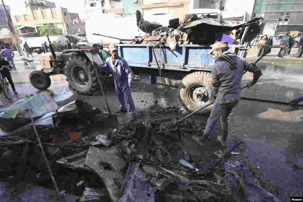 Municipality workers clean debris at the site of a bomb attack in Karbala, Iraq, November 29, 2012.