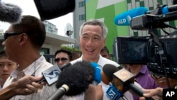 Singapore's Prime Minister Lee Hsien Loong talks to journalists after voting at a polling station in Singapore, Friday, Sept. 11, 2015.