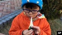 지난달 13일 새해 축제를 준비 중인 일본 요코하마의 공원에서 한 소년이 모치를 먹고 있다. (자료사진)