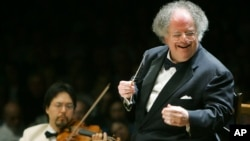 "FILE - Boston Symphony Orchestra music director James Levine, right, conducting the symphony on its opening night performance at Tanglewood in Lenox., Massachusetts, July 7, 2006. The Met Opera has fired the music director emeritus, finding ""credible evidence"" of ""sexually abusive"" conduct."