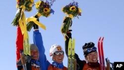 De gauche à droite, la médaillée d'argent Larissa Lazutina, de la Russie, la médaillée d'or Olga Danilova, de la Russie, et la médaillée de bronze Beckie Scott, du Canada, célébrant leur victoire en cross-country de 5 km aux Jeux olympiques d'hiver.