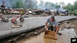 Mark Lester membersihkan kotak dengan air sungai kecil menyusul banjir parah di White Sulphur Springs, West Virginia (24/6). (AP/Steve Helber)
