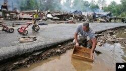 马克·莱斯特6月24日在所居住的西弗吉尼亚州白硫磺泉镇遭遇严重洪水之后,正在进行清理,用溪水清洗一个盒子。