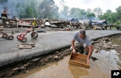 Mark Lester cleans out a box with creek water as he cleans up from severe flooding in White Sulphur Springs, W. Va., June 24, 2016.