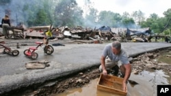 西维吉尼亚州的一名受灾居民在路边的水里清洗被水淹的家具。(2016年6月24日)