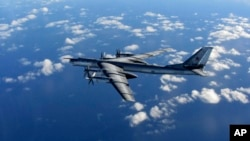 FILE - In this photo provided by Britain's Royal Air Force and taken on Oct. 29, 2014, a Russian military long range bomber aircraft photographed by an intercepting RAF quick reaction Typhoon (QRA) flies in international airspace.