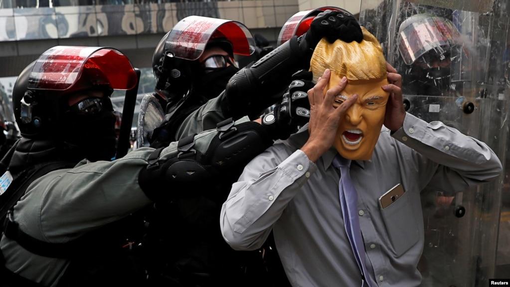 Một người biểu tình đeo mặt nạ hình ông Trump bị cảnh sát chống bạo động TQ đẩy rlùi trong một cuộc biểu tình ở Causeway Bay, Hong Kong.