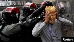 Seorang pedemo mengenakan topeng Presiden AS Donald Trump bentrok dengan polisi saat demonstrasi di distrik Causeway Bay, Hong Kong, China, 29 September 2019.