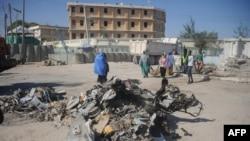 Des passants sur le site bombardé à Mogadiscio près du minitère du travail, le 23 mars 2019.