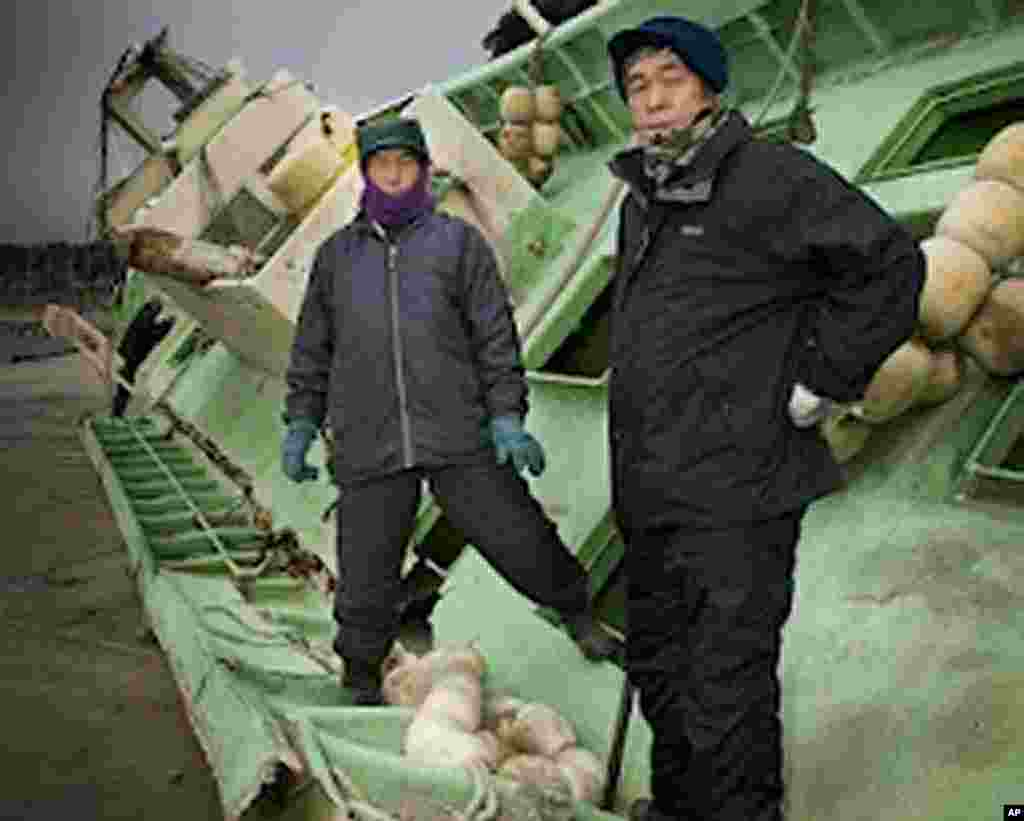 Fisherman with their tsunami-damaged boat, Obama Port, Fukushima prefecture, Japan, Matsushima Bay, Japan. (Photo by Mark Edward Harris)