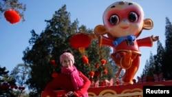 一名女子在北京地坛公园前为迎接中国新年猴年到来树立的猴像前留影 (2016年2月)