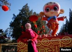 在春节前夕,在北京地坛庙会,一位妇女在猴子造型前面摆姿势照相(2016年2月5日)