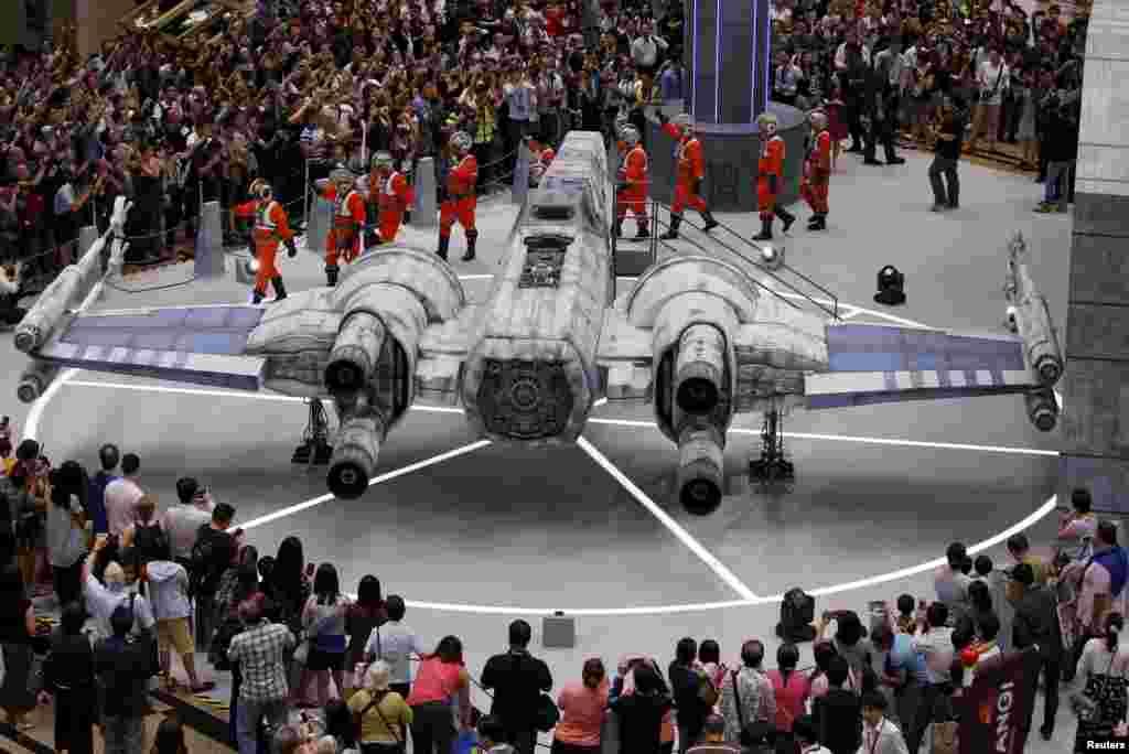 "Warga menonton model pesawat tempur ""Star Wars X-wing"" yang sesuai ukuran aslinya, dipamerkan di bandara Changi, Singapura."