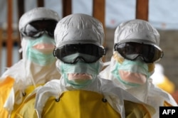Health care workers in protective suits leave a high-risk area at a Monrovia hospital run by Doctors Without Borders on Aug. 30, 2014.