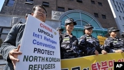 "South Korean activists stage a protest outside the Chinese embassy in Seoul urging Beijing to stop repatriating refugees who flee hunger or repression in North Korea. About 30 activists including former refugees chanted slogans like ""Stop forced repatriat"