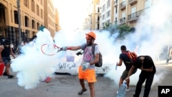 An anti-government protester uses a a tennis racket to hit back a tear gas canister towards at riot policemen during a protest following last Tuesday's massive explosion which devastated Beirut, Lebanon, Monday, Aug. 10, 2020.