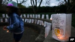 FILE - A volunteer helps setup lights in paper bags decorated with messages for the deceased during an Out of the Darkness Walk event organized by the Cincinnati Chapter of the American Foundation for Suicide Prevention in Sawyer Point park, Oct. 15, 2017, in Cincinnati.