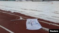 Một lá cờ mang logo Thế vận hội Mùa đông 2018 nằm trên mặt đất tại một địa điểm được đề xuất xây sân vận động Olympic ở Pyeongchang, 10/2/2015.