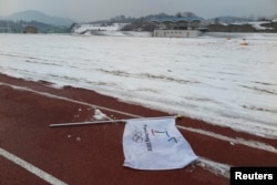 A flag bearing the logo of 2018 Winter Olympic Games lies on the ground at the proposed site of the Olympic Stadium near the Alpensia Resort in the mountain cluster of PyeongChang, February 10, 2015.