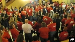 Dozens of teachers crowd into a third-floor wing of the Kansas Statehouse to lobby for a bill increasing funding for public schools, April 7, 2018, in Topeka, Kan. Legislators face a Kansas Supreme Court mandate to boost education funding.
