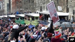New England fans cheer as the team passes by in a procession of duck boats during a parade in Boston to honor the Patriots' Super Bowl XLIX victory over the Seattle Seahawks, Feb. 4, 2015.